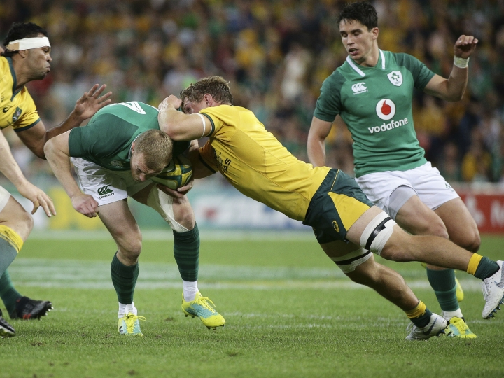 Keith Earls, center left, of Ireland is tackled by Michael Hooper, center right, of Australia during the International rugby match between Australia and Ireland in Brisbane, Australia, Saturday, June 9, 2018. (AP Photo/Tertius Pickard)