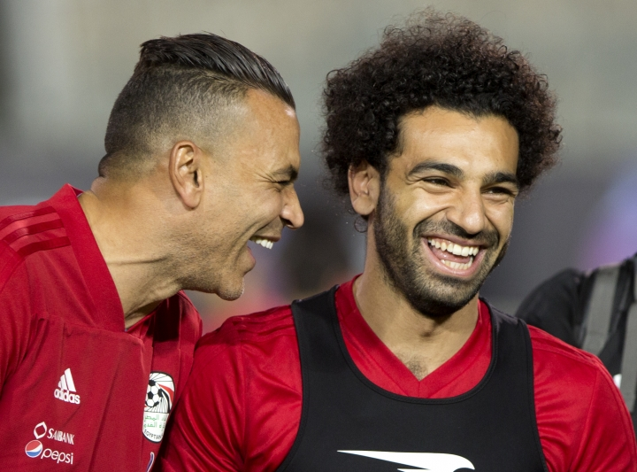 Egyptian national soccer team player and Liverpool's star striker Mohammed Salah, right, shares a laugh with goalkeeper Essam El Hadary during Egypt's final practice for the World Cup soccer tournament, at Cairo Stadium in Cairo, Egypt, Saturday, June 9, 2018. Thousands of fans gathered at Cairo's main stadium Saturday to watch Egypt's last home practice before flying to Grozny, Chechnya, where they'll set up base during their World Cup campaign in Russia. (AP Photo/Amr Nabil)