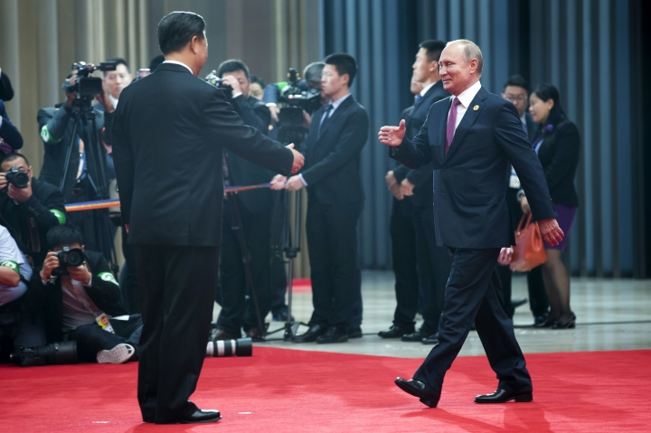 Chinese President Xi Jinping, left, greets Russian President Vladimir Putin during an arriving ceremony at the Shanghai Cooperation Organization (SCO) Summit in Qingdao in eastern China's Shandong Province Sunday, June 10, 2018. (AP Photo/Alexander Zemlianichenko)