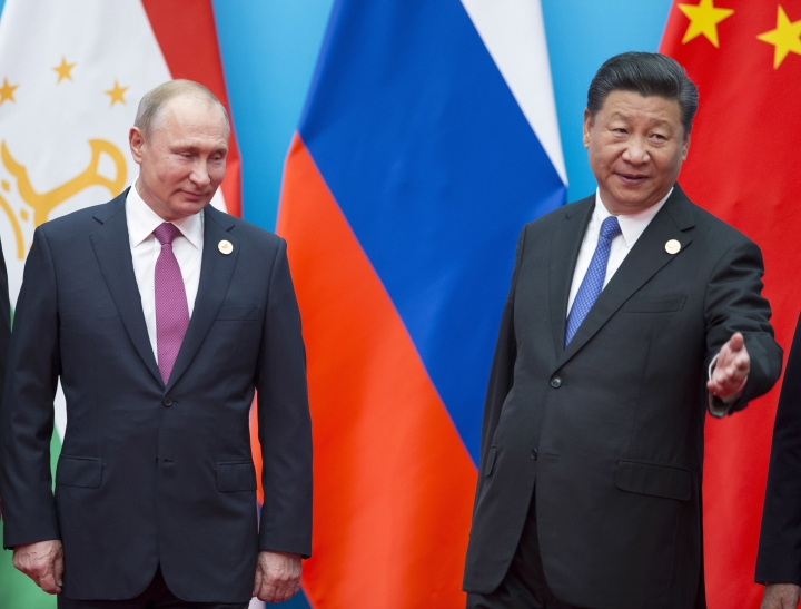 Chinese President Xi Jinping, right, welcomes Russian President Vladimir Putin for talks at the Shanghai Cooperation Organization (SCO) Summit in Qingdao in eastern China's Shandong Province Sunday, June 10, 2018. (AP Photo/Alexander Zemlianichenko)