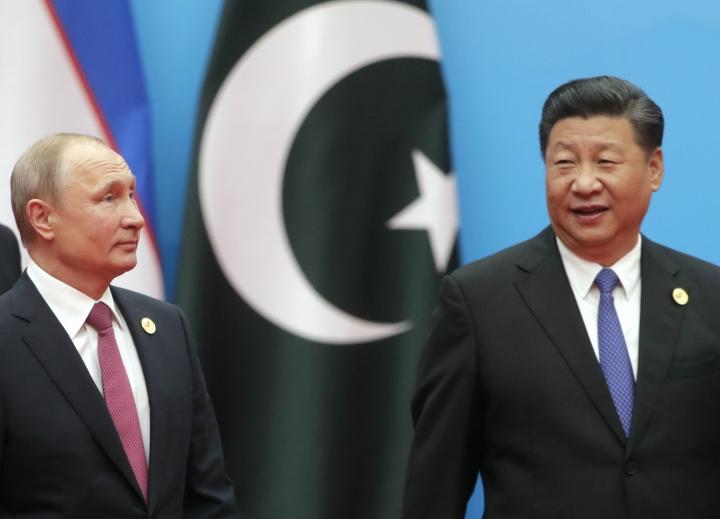 Russian President Vladimir Putin, left, and Chinese President Xi Jinping walk to attend talks at the Shanghai Cooperation Organization (SCO) Summit in Qingdao in eastern China's Shandong Province Sunday, June 10, 2018. (Mikhail Metzel, Sputnik, Kremlin Pool Photo via AP)