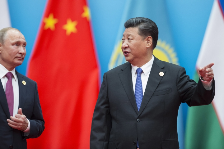 Chinese President Xi Jinping, right, points as he and Russian President Vladimir Putin walk to attend talks at the Shanghai Cooperation Organization (SCO) Summit in Qingdao in eastern China's Shandong Province Sunday, June 10, 2018. (AP Photo/Alexander Zemlianichenko)