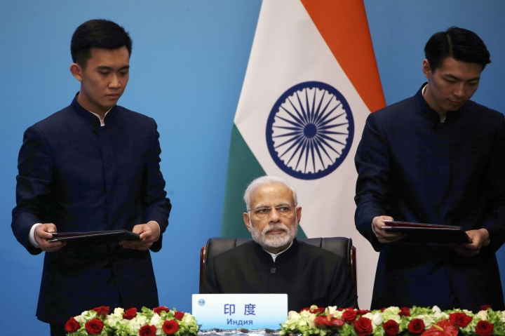 """Workers prepares to hand agreements to Indian Prime Minister Narendra Modi during a signing ceremony for the Shanghai Cooperation Organization (SCO) Summit in Qingdao in eastern China's Shandong Province, Sunday, June 10, 2018. Xi extolled free trade and criticized """"selfish, short-sighted"""" policies during the closely orchestrated gathering, standing in stark contrast with the G-7 summit that ended in disarray over trade tensions. (AP Photo/Dake Kang)"""