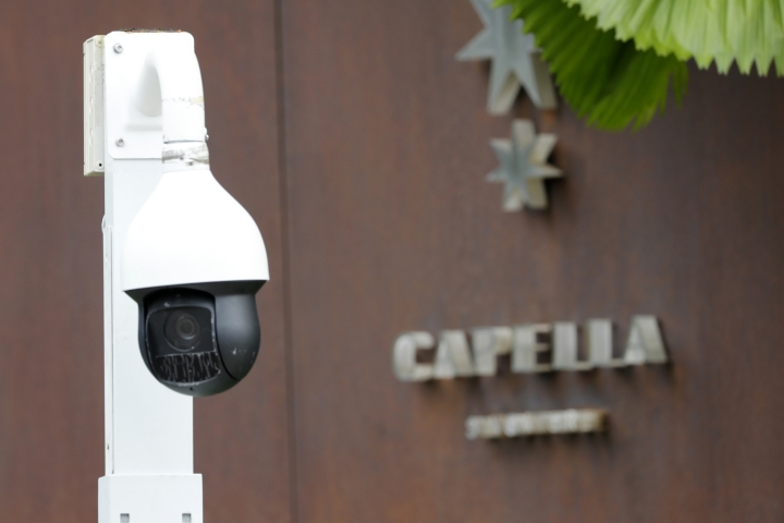 In this Saturday, June 9, 2018, photo, a surveillance camera is seen at the entrance to the driveway of Capella Hotel in Sentosa, Singapore. A new surveillance camera is installed and restaurants closed on Singapore's Sentosa Island, a popular tropical getaway now easing into the political spotlight ahead of a summit between U.S. President Donald Trump and North Korean leader Kim Jong Un. (AP Photo/Wong Maye-E)