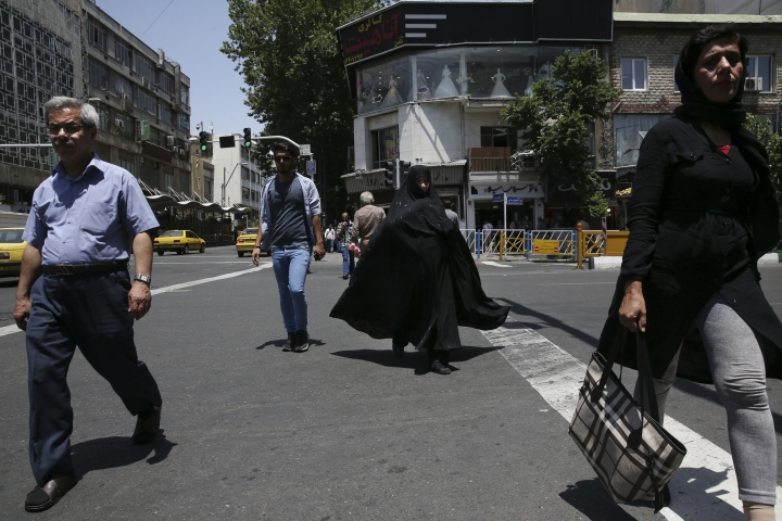 """Iranian pedestrians cross Jomhouri-e-Eslami (Islamic Republic) St. in downtown Tehran, Iran, Saturday, June 9, 2018. For Iran, the so-called """"Axis of Evil"""" has become a lonely party of one as President Donald Trump prepares for direct talks with North Korea. With Saddam Hussein overthrown and Kim Jong Un now preparing for planned meeting in Singapore with Trump, Iran remains the last renegade among former President George W. Bush's grouping of nations opposed to the U.S. It also comes after Trump pulled out of the nuclear deal, worsening Iran's already-anemic economy. (AP Photo/Vahid Salemi)"""