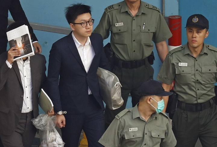 Hong Kong Activist Edward Leung, second left, is escorted by Correctional Services officers at a prison yard before boarding a bus to take him to high court for sentencing in Hong Kong, Monday, June 11, 2018. A Hong Kong court has sentenced Leung to six years in prison for his part in a violent nightlong clash with police over illegal street food hawkers two years ago. (AP Photo/Vincent Yu)