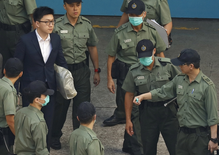 Hong Kong Activist Edward Leung, top left, is escorted by Correctional Services officers at a prison yard before boarding a bus to take him to high court for sentencing in Hong Kong, Monday, June 11, 2018. A Hong Kong court has sentenced Leung to six years in prison for his part in a violent nightlong clash with police over illegal street food hawkers two years ago. (AP Photo/Vincent Yu)