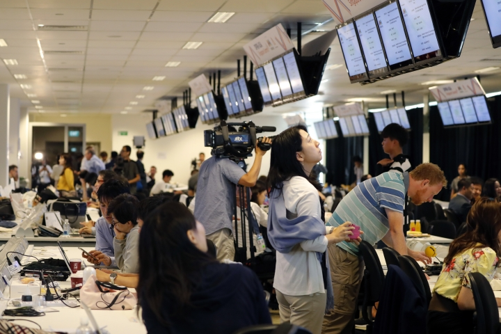 Members of the press watch a live telecast of U.S. President Donald Trump's bilateral meeting with Singapore's Prime Minister Lee Hsien Loong on Monday, June 11, 2018, in Singapore, at the international media center. (AP Photo/Wong Maye-E)
