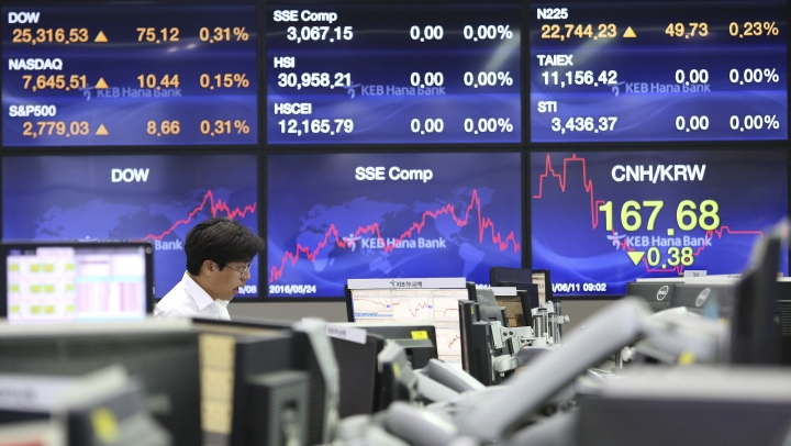 A currency trader watches monitors at the foreign exchange dealing room of the KEB Hana Bank headquarters in Seoul, South Korea, Monday, June 11, 2018. Asian markets were mixed Monday before President Donald Trump planned to meet North Korean leader Kim Jong Un and after his outburst at Canada's prime minister over trade. (AP Photo/Ahn Young-joon)