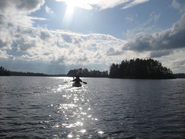 This Sept. 16, 2017 photo shows two canoeists paddling in the late afternoon on Disappointment Lake, one of more than a thousand lakes in Minnesota's Boundary Waters Canoe Area Wilderness. The glacier-carved lakes have black, glossy surfaces, and plenty of walleyes, pikes, and loons. (Giovanna Dell'Orto via AP)