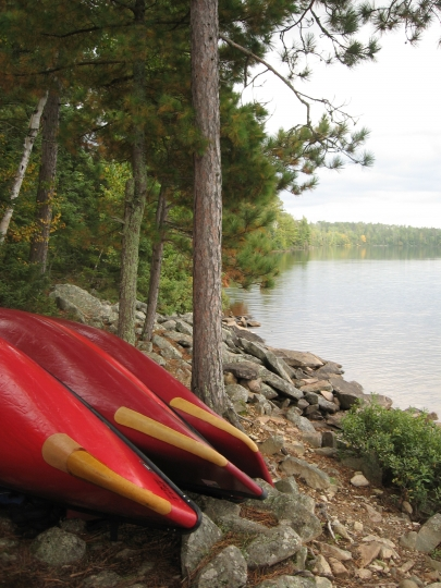 This Sept. 16, 2017 photo shows canoes pulled out of the water for the night at a campsite on Parent Lake in Minnesota's Boundary Waters Canoe Area Wilderness. Limited numbers of permits are granted to camp in the wilderness, and once a group of nine people and four canoes maximum reaches a campsite, it's theirs alone. (Giovanna Dell'Orto via AP)