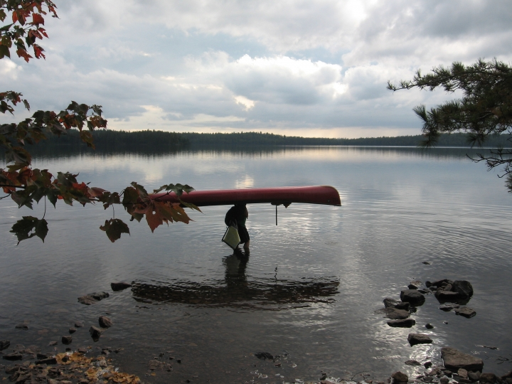 This Sept. 16, 2017 photo shows a visitor to Minnesota's Boundary Waters Canoe Area Wilderness getting ready to put the 16.5-foot canoe back in the water after carrying it overhead across a portage to Parent Lake. Hundreds of years ago, Native Americans and fur traders carved these trails through the forests connecting the more than one thousand lakes in the area. (Giovanna Dell'Orto via AP)
