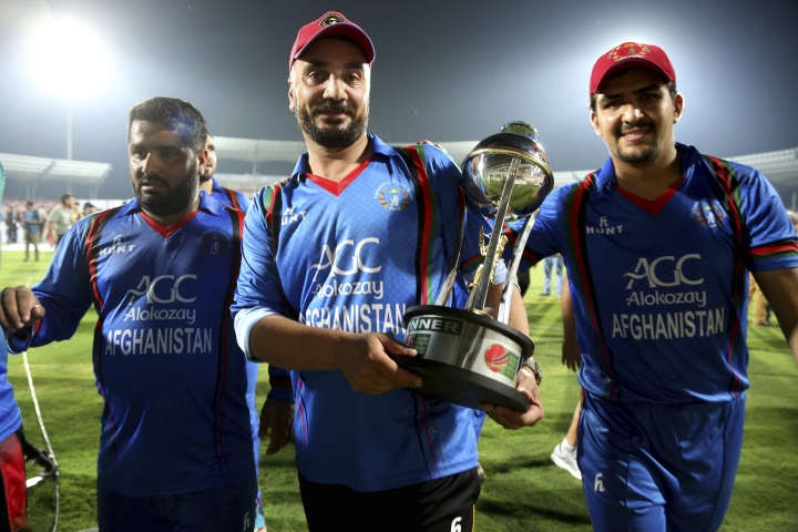 Afghanistan cricket players coming back to the pavilion with the winning trophy of T20 cricket match between Afghanistan and Bangladesh in Dehraduni, India, Friday, June 8, 2018, Afghanistan win the series by 3-0. (AP Photo/Anupam Nath)