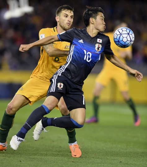 FILE - In this Tuesday, Oct. 11, 2016 filer, Japan's Shinji Kagawa, right, and Australia's Matthew Spiranovic compete for the ball during their World Cup qualifying match in Melbourne, Australia. (AP Photo/Andy Brownbill, File)