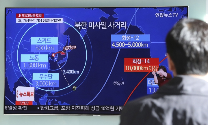 """FILE - This Nov. 29, 2017, file photo, a man watches a TV screen showing a local news program reporting about North Korea's missile launch, at the Seoul Railway Station in Seoul, South Korea. Tuesday's meeting on June 12, 2018 in Singapore between North Korean leader Kim Jong Un and U.S. President Donald Trump comes after a sharp turn in North Korea's diplomacy, from rebuffing proposals for dialogue last year to embracing and even initiating them this year. The change may reflect a new thinking about its nuclear deterrence strategy, and how best to secure the ultimate goal of protecting Kim's rule. The letters on TV read: """"North Korea's missile range."""" (AP Photo/Lee Jin-man, File)"""