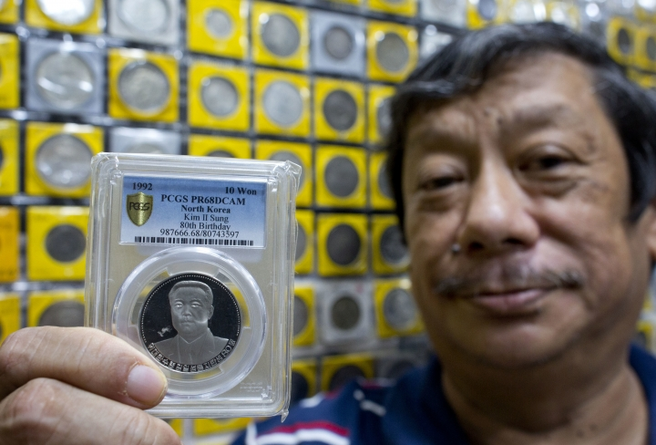 """In this Monday, June 11, 2018, photo, rare coin collector and dealer Harry Ng displays a North Korean coin depicting Kim II Sung, founding leader of North Korea issued to commemorate his 80th Birthday in 1992 from his collection in Singapore. Stamped with images of """"Eternal President"""" Kim Il Sung, national monuments or ballistic missiles, coins minted in North Korea are renowned among collectors for their scarcity, partly due to international sanctions that outlaw them from being auctioned. (AP Photo/Gemunu Amarasinghe)"""