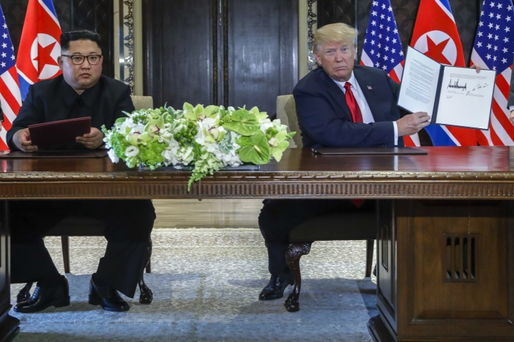 U.S. President Donald Trump holds up the document that he and North Korea leader Kim Jong Un just signed at the Capella resort on Sentosa Island Tuesday, June 12, 2018 in Singapore. (AP Photo/Evan Vucci)
