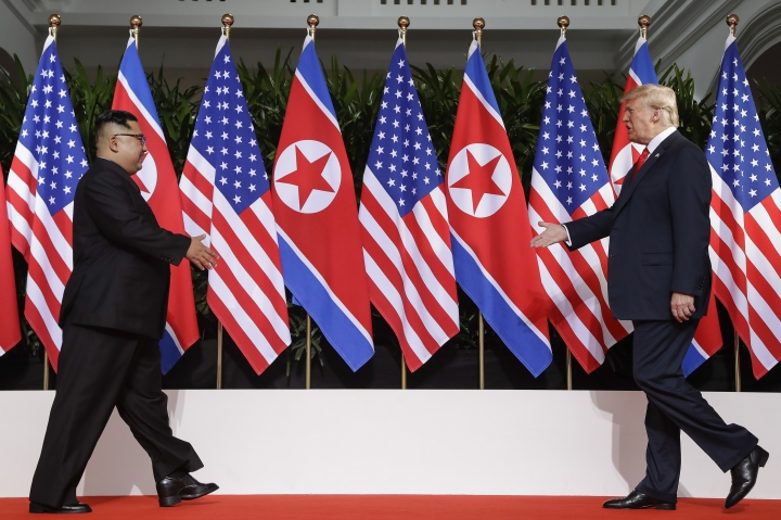 U. S. President Donald Trump and North Korea leader Kim Jong Un walks toward each other at the Capella resort on Sentosa Island Tuesday, June 12, 2018 in Singapore. (AP Photo/Evan Vucci)
