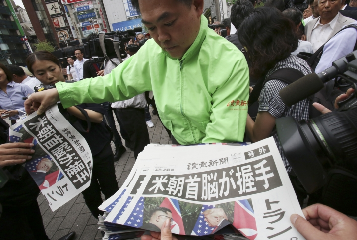 """A staff of a Japanese news paper Yomiuri distributes an extra edition of the newspaper reporting about the summit between U.S. President Donald Trump and North Korean leader Kim Jong Un in Singapore, at Shimbashi Station in Tokyo, Tuesday, June 12, 2018. President Trump and North Korea's Kim came together for a momentous summit Tuesday that could determine historic peace or raise the specter of a growing nuclear threat, with Trump pledging that """"working together we will get it taken care of."""" (AP Photo/Koji Sasahara)"""
