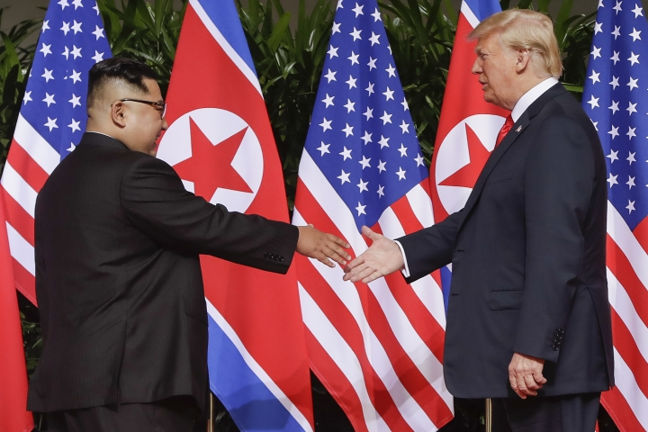 U.S. President Donald Trump reaches to shake hands with North Korea leader Kim Jong Un at the Capella resort on Sentosa Island Tuesday, June 12, 2018 in Singapore. (AP Photo/Evan Vucci)