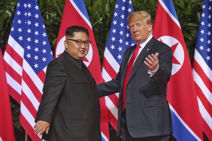 U. S. President Donald Trump gestures toward the media with North Korea leader Kim Jong Un at the Capella resort on Sentosa Island Tuesday, June 12, 2018, in Singapore. (Kevin Lim/The Straits Times via AP)