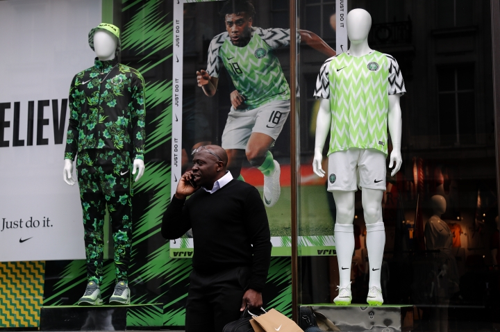 In this June 5, 2018 photo a man stands in front of a Nigerian national soccer team jersey is on display at a shop in London. With just days to go before the FIFA World Cup, some winners and losers have emerged among the often wild and wacky team jerseys. (AP Photo/Frank Augstein)