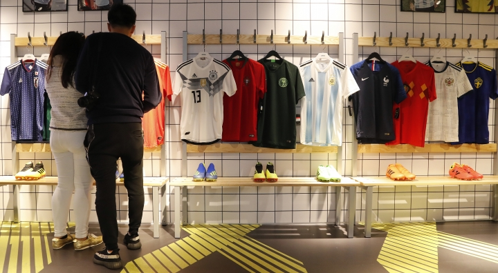 In this June 5, 2018 photo customers look at different national soccer team jerseys that are on display at a shop in London. With just days to go before the FIFA World Cup, some winners and losers have emerged among the often wild and wacky team jerseys. (AP Photo/Frank Augstein)