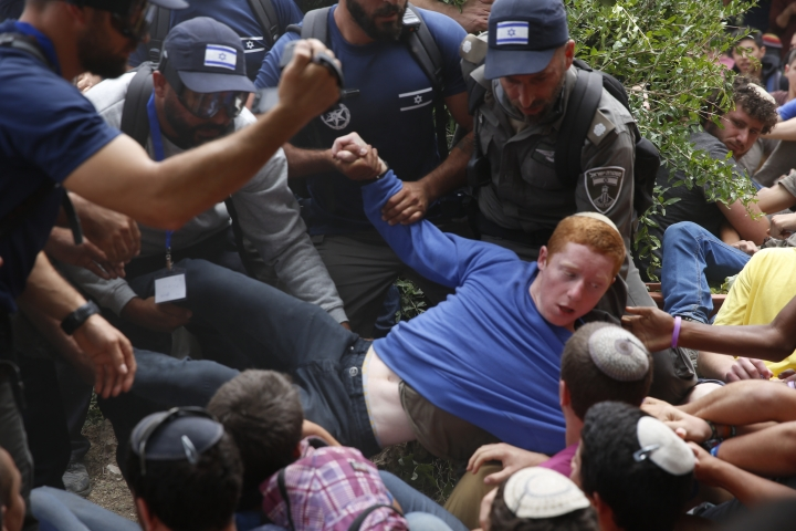 Israeli police evict Jewish settlers at the West Bank settlement of Netiv Avot, Tuesday, June 12, 2018. Police say they have started the evacuation Tuesday of the Netiv Avot unauthorized outpost in Gush Etzion. Israel's Supreme Court ordered the eviction because the homes were built on private Palestinian land. (AP Photo/Ariel Schalit)