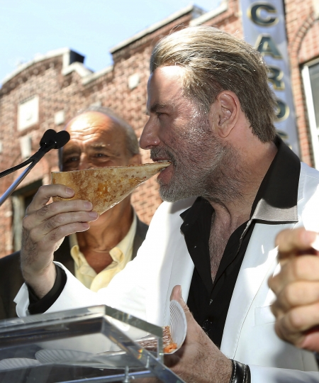 "This image released by Starpix shows actor John Travolta, star of the upcoming film ""Gotti,"" eating a slice of pizza from Lenny's Pizzeria in the Brooklyn borough of New York on Tuesday, June 12, 2018. The pizzeria was highlighted in the 1977 blockbuster ""Saturday Night Fever"" when Travolta's Tony Manero character ordered two slices and ate them one on top of the other as he walked down the street. The restaurant has become a popular tourist spot with people still ordering the double-decker slices. (Patrick Lewis/Starpix via AP)"