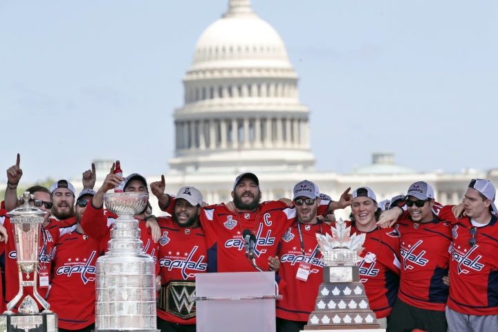 Washington Capitals Alex Ovechkin, center, from Russia, sings with teammates during the NHL hockey team's Stanley Cup victory celebration, Tuesday, June 12, 2018, at the National Mall in Washington. The U.S. Capitol rises in the background. (AP Photo/Jacquelyn Martin)