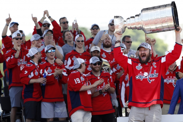 Washington Capitals Alex Ovechkin, from Russia, right, holds up the Stanley Cup during a victory rally for the Washington Capitals in celebration of winning the Stanley Cup, Tuesday, June 12, 2018, on the National Mall in Washington. (AP Photo/Jacquelyn Martin)