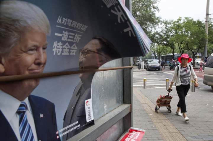 A Chinese woman pulls a trolley bag past a Chinese magazine cover showing U.S. President Donald Trump and North Korean leader Kim Jong Un at a newsstand in Beijing, China, Wednesday, June 13, 2018. The outcome of the Singapore summit between President Donald Trump and North Korean leader Kim Jong Un was good news for one absent but key player: China. (AP Photo/Ng Han Guan)