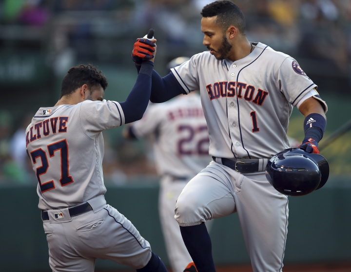 Houston Astros' Carlos Correa, right, celebrates with Jose Altuve (27) after hitting a home run off Oakland Athletics' Daniel Mengden during the second inning of a baseball game Tuesday, June 12, 2018, in Oakland, Calif. (AP Photo/Ben Margot)