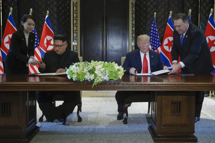 North Korea leader Kim Jong Un and U.S. President Donald Trump prepare to sign a document at the Capella resort on Sentosa Island Tuesday, June 12, 2018 in Singapore. (AP Photo/Evan Vucci)