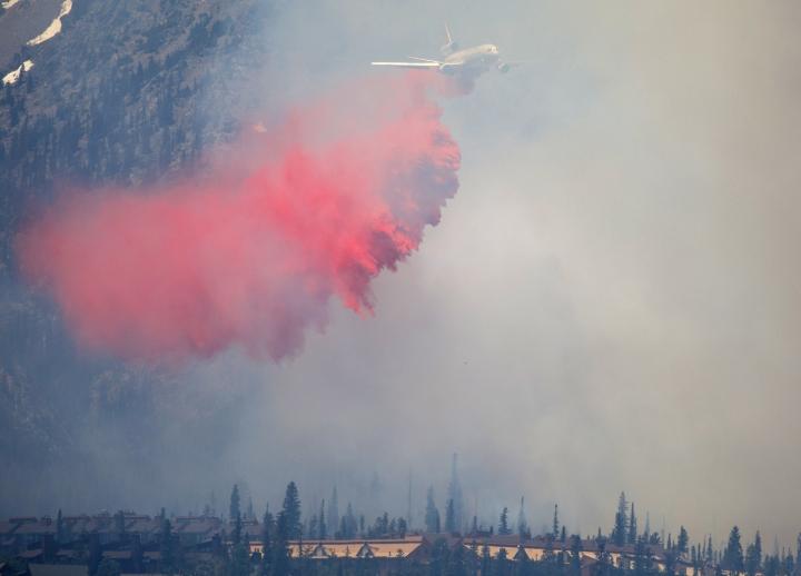 A fire retardant aircraft flies over a wild fire in the Wildernest neighborhood near Silverthorne, Colo., Tuesday, June 12, 2018. (Hugh Carey/Summit Daily News via AP)