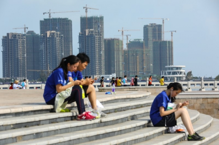 FILE PHOTO: People sit on steps against a backdrop of residential buildings under construction, in Haikou, Hainan province, China April 22, 2018. Picture taken April 22, 2018.  REUTERS/Stringer