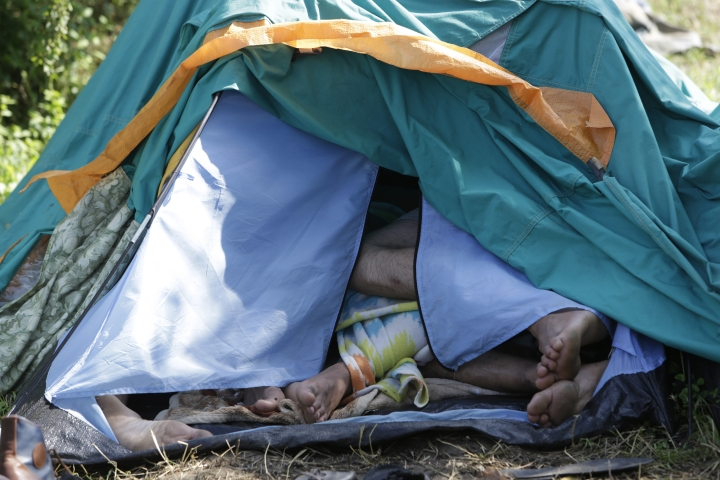 In this photo taken on Sunday, June. 10, 2018, migrants sleep inside a tent in a make-shift tent camps in Velika Kladusa, 400 kms north west of Bosnian capital of Sarajevo. The restaurant owner Asim Latic from northwestern Bosnia in February closed down his pizzeria for regular guests and is now serving only meals for migrants passing through the Balkan nation while trying to reach Western Europe. (AP Photo/Amel Emric)