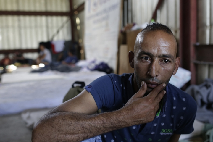 In this photo taken on Sunday, June 10, 2018, a migrant man from Libya waits in the shade of a warehouse for lunch, in Velika Kladusa, 400 kms north west of Bosnian capital of Sarajevo, on Saturday, June. 9, 2018. The restaurant owner Asim Latic from northwestern Bosnia in February closed down his pizzeria for regular guests and is now serving only meals for migrants passing through the Balkan nation while trying to reach Western Europe. (AP Photo/Amel Emric)