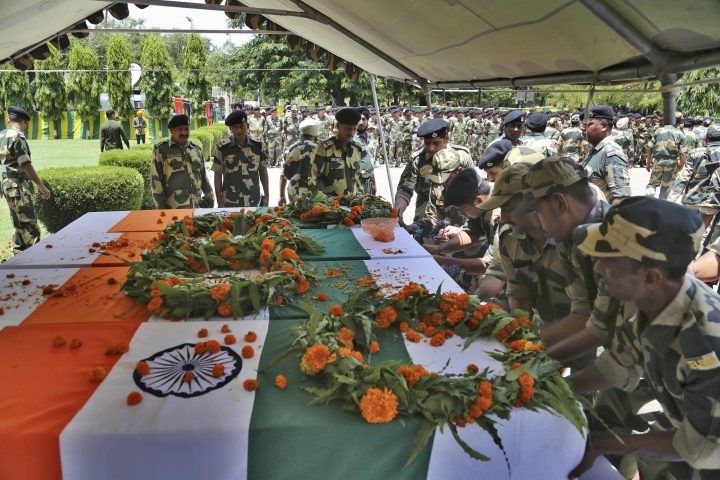Indian Border Security Force (BSF) soldiers pay tribute to four of their colleagues who were killed early Wednesday during a wreath-laying ceremony at the BSF headquarters in Jammu, India, Wednesday, June 13, 2018. Indian and Pakistani forces fired along the highly militarized frontier in disputed Kashmir early Wednesday after Pakistani firing killed at least four Indian paramilitary soldiers and injured three others on border patrol, Indian officials said. (AP Photo/Channi Anand)