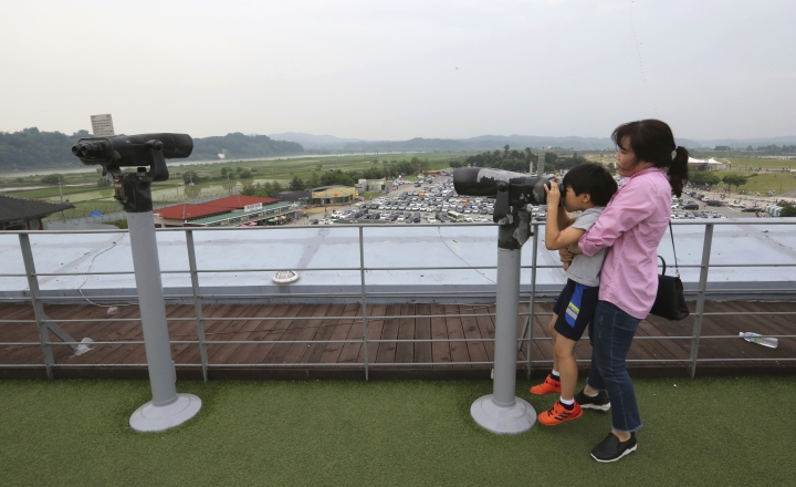 A mother holds her son as he looks through binoculars towards North Korea at the Imjingak Pavilion in Paju near the border village of Panmunjom, South Korea, Wednesday, June 13, 2018. While South Koreans cheered with hope and China saw an opening to discuss lifting sanctions on North Korea, some countries in Europe and the Mideast cautioned Tuesday that it was premature to judge U.S. President Donald Trump and North Korean leader Kim Jong Un's summit a success. (AP Photo/Ahn Young-joon)