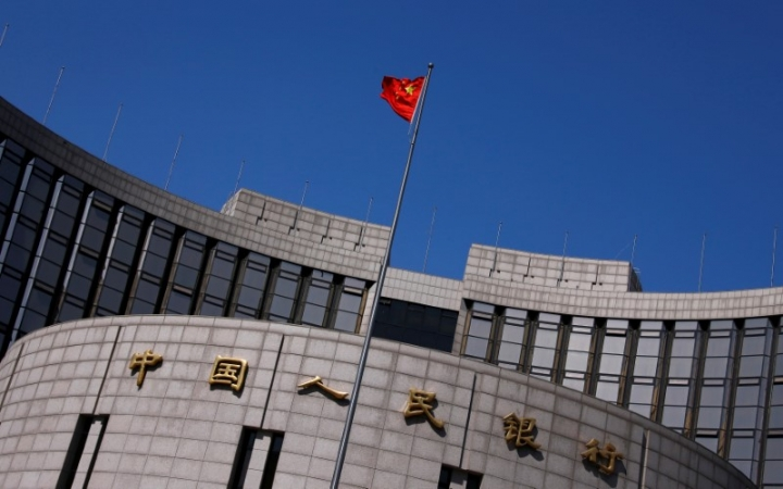 FILE PHOTO: A Chinese national flag flutters outside the headquarters of the People's Bank of China, the Chinese central bank, in Beijing, China April 3, 2014. B REUTERS/Petar Kujundzic/File Photo