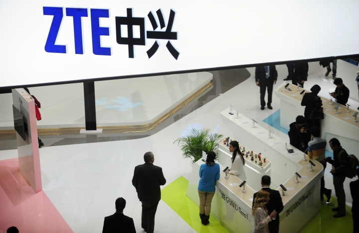 FILE - In this Wednesday, Feb. 26, 2014, file photo, people gather at the ZTE booth at the Mobile World Congress, the world's largest mobile phone trade show in Barcelona, Spain. Shares in ZTE Corp. have fallen 42 percent in Hong Kong after the Chinese telecoms equipment maker agreed to pay a $1 billion penalty to the U.S. government and replace its top managers. (AP Photo/Manu Fernandez, File)
