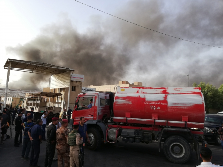 Iraqi security forces and firemen gather as smoke rises from a fire that broke out at Baghdad's largest ballot box storage site, where ballots from Iraq's May parliamentary elections are stored, in Baghdad, Iraq, Sunday, June 10, 2018. The ballots are part of a manual recount of votes, mandated in a law passed by the Iraqi parliament last Wednesday. (AP Photo/Karim Kadim)
