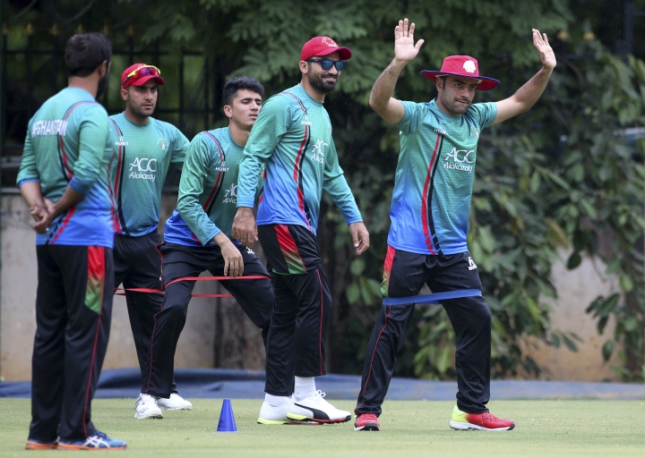 Afghanistan cricketer Rashid Khan, right, performs stretching exercises with teammates during a training session ahead of one-off test match against India in Bangalore, India, Wednesday, June 13, 2018. (AP Photo/Aijaz Rahi)