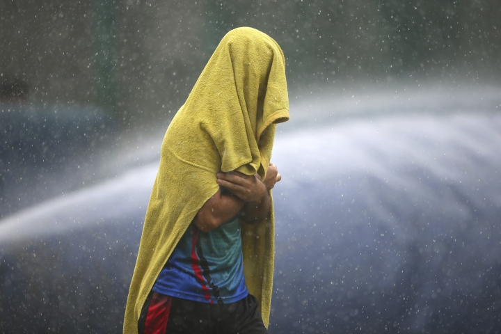 An unidentified player of Afghanistan cricket team covers himself with a towel as he runs for shelter during sudden rains at a training session ahead of one-off test match against India in Bangalore, India, Wednesday, June 13, 2018. (AP Photo/Aijaz Rahi)