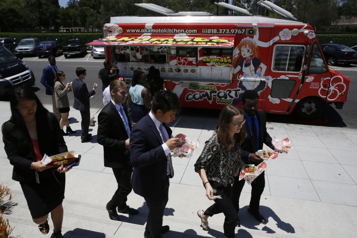 In this Friday, June 8, 2018, photo customers get their lunch at the Japanese food truck Okamoto Kitchen in Beverly Hills, Calif. Rather than sushi and tempura, they serve meat, fish and sandwiches using traditional Japanese flavors like ponzu. (AP Photo/Damian Dovarganes)