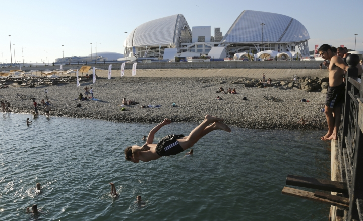 A boy jumps into the black sea in front of the Fisht stadium, which will host some 2018 World Cup matches in Sochi, Russia, Monday, June 11, 2018. (AP Photo/Andre Penner)