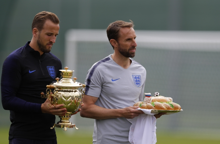England head coach Gareth Southgate, holds a loaf of bread and England's Harry Kane holds a Russian tea urn they received during a traditional Russian greeting before the start of the first training session for the England team at the 2018 soccer World Cup at the Spartak Zelenogorsk stadium, Zelenogorsk near St. Petersburg, Russia, Wednesday, June 13, 2018. (AP Photo/Alastair Grant)