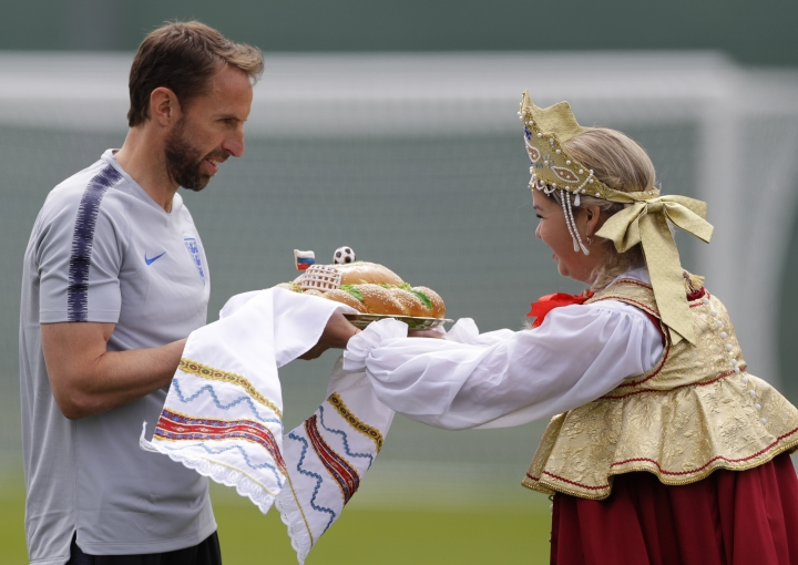 England head coach Gareth Southgate, receives the traditional Russian greeting of bread from a woman in traditional costume before the start of the first training session for the England team at the 2018 soccer World Cup at the Spartak Zelenogorsk stadium, Zelenogorsk near St. Petersburg, Russia, Wednesday, June 13, 2018. (AP Photo/Alastair Grant)