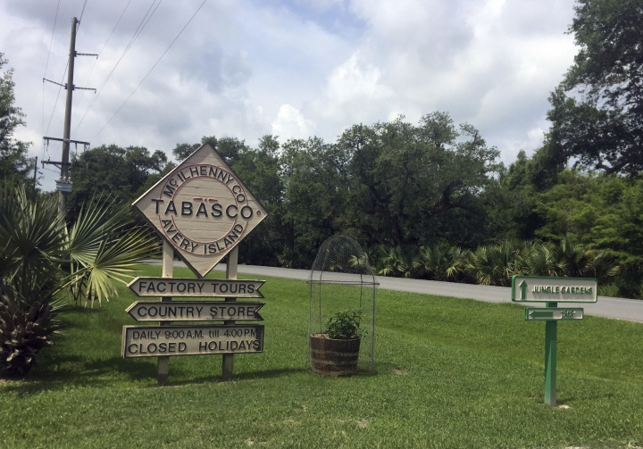 This June 4, 2018 photo shows a sign directing visitors to attractions on Avery Island in Louisiana, where Tabasco sauce is made. The product was first made in 1868 and celebrates its 150th year this year. Visitors can see exhibits about the history of the famous pepper sauce, view the factory production, enjoy free tastings and samples, shop, dine and also tour a nature preserve called Jungle Gardens. (AP Photo/Beth J. Harpaz)
